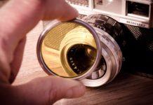 Stary aparat fotograficzny widziany przez pomarańczową soczewkę